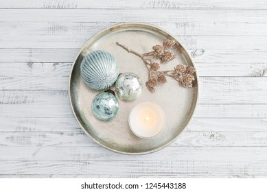 Tray with christmas decorations and candle on white wooden background, top view