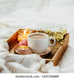 Tray of coffee and candles with warm plaid on white bedding . Breakfast in bed.  Scandinavian style.  Flat lay, top view