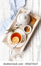 Tray with cup of hot black tea, lemon and honey on white rustic wooden background. Breakfast concept. Top view