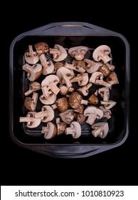 Tray of cut mushrooms on a dark background