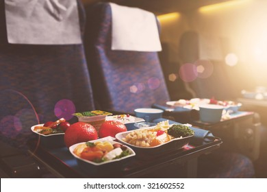 Tray with delicious healthy food on the plane, business class travel. Tasty Lunch served in the aircraft interior. Sun shining through the airplane window. Lens Flare.
