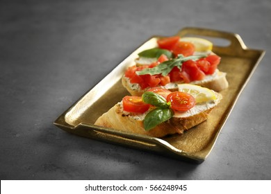 Tray with delicious Italian toasts on grey table