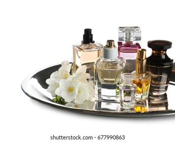 Tray with different bottles of perfume and flowers on white background
