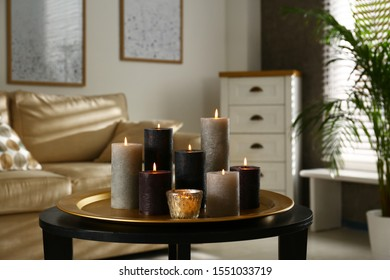 Tray with different burning candles on table in room