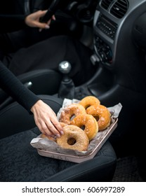 A tray of doughnuts put on the trunk of the cabriolet car