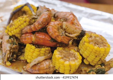 A tray is filled with corn on the cob, and shrimp. Everything is seasoned to perfection with spices.