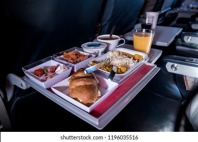 Tray of food. The passenger eats food on Board the plane on the background of the window. Meals on the plane. Different sets of food on the folding table.