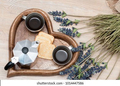 A tray of a form of a saddle with two cups of coffee, a coffee maker, biscuits and flowers. The concept of Valentines Day.