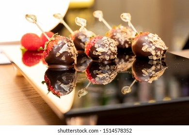 A tray of freshly dipped chocolate covered strawberries.