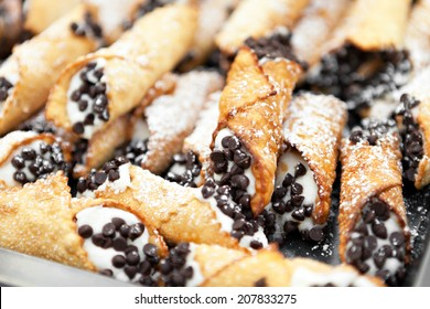 Tray full of freshly filled cannolis with chocolate chips and confectioners sugar. Shallow depth of field.