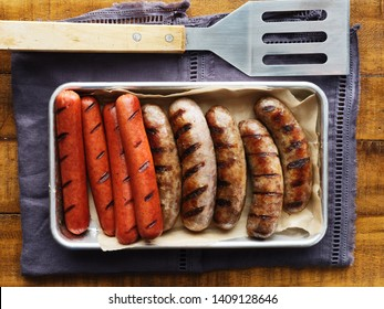 tray of grilled hot dogs and bratwursts on tray in top down composition
