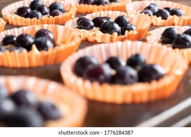 a tray of homemade blueberry muffins in a baking tray before baking