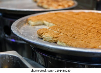 A tray of kunafah, also spelled kanafeh, cut into pieces, ready to be served in an Arabic bakery in Dubai, United Arab Emirates.  Kunafah is a cheese pie topped with a crispy noodle pastry and drizzle