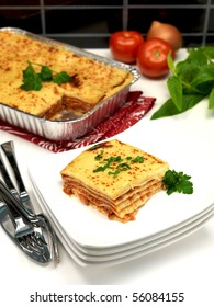 A tray of lasagna on a kitchen bench being plated up
