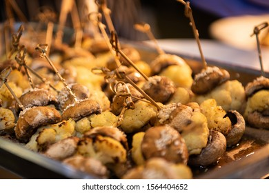 Tray of mini cauliflower vegan burgers, with bamboo skewer. Under heat lamp prior to being served. Mostly brown in colour. Selective focus on the mid point.