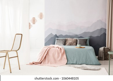 Tray with mugs on a cozy, blue bed with a pastel pink blanket by a landscape wallpaper in a bright bedroom interior