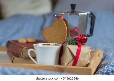tray with old books, coffee and gift on the bed