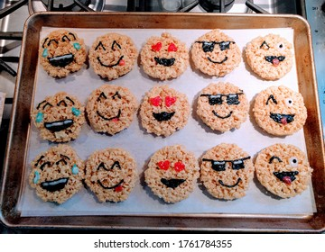 Tray of rice krispie puffed rice treats made to look like emoji faces