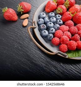 Tray with ripe organic bilberry raspberry strawberry and almonds set on slate closeup