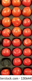 A tray of ripe red tomatoes.