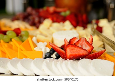 Tray of sliced cheeses and fruits, selective focus on the sliced strawberries