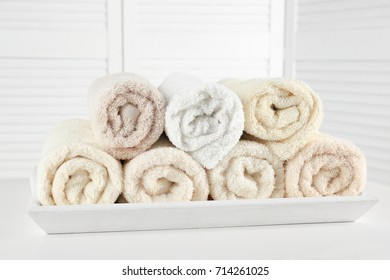 Tray with soft rolled towels on table