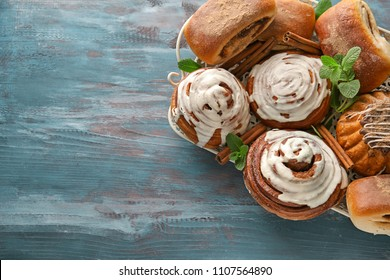 Tray with sweet cinnamon buns on wooden table