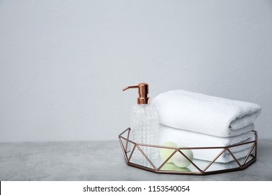 Tray with towels and toiletries on table against grey background
