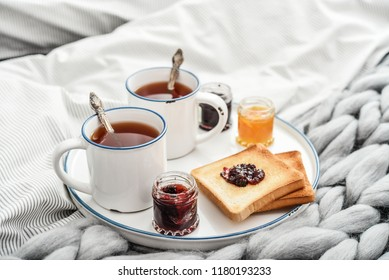 Tray with two cups of black  tea, different jam in jars and toasts on bed at breakfast time closeup