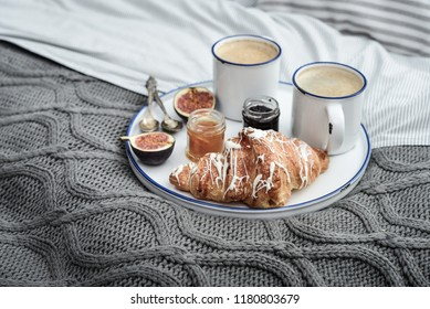 Tray with two cups of coffee, different jam in jars and croissant on bed at breakfast time