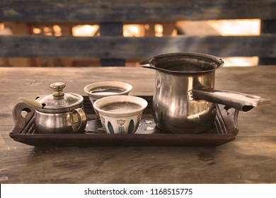 A tray with two Lebanese traditional coffee cups with a Turkish coffee Kettle.