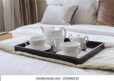 tray of white tea set on bed in bedroom