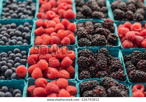 Trays of fresh berries on display at a local market.
