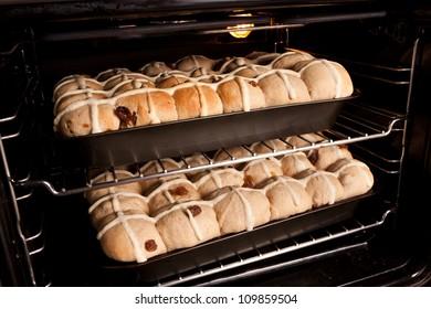 Trays of homemade fresh hot cross buns baking in oven