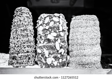 Trdelnik is a kind of spit cake. It is made from rolled dough that is wrapped around a stick, then grilled and topped with sugar and walnut mix. Black and white photo.