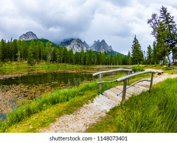 Tre Cime di Lavaredo Mountain reflected in water od Antorno Lake, Dolomites, Italy. Tre Cimes di Lavaredo and Antorno Lake, Italy. Wooden bridge mountain lake
