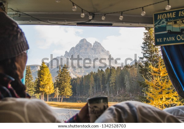 Tre Cimes di Laverado Dolomites, Italy - October 9, 2018: Woman enjoys cup of coffee out back of van while living the nomadic van life (vanlife) lifestyle in Europe on a cold autumn morning.
