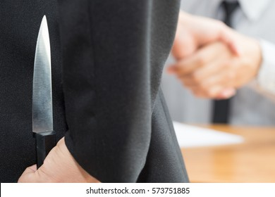 Treachery, two business making handshake a deal but hiding knives