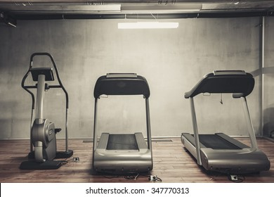 Treadmills set in gym interior. Fitness club with equipment. Sports background with rough concrete walls