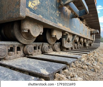 Treads of a large backhoe on road base and gravel