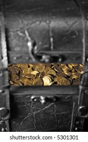 Treasure chest in black and white, with gold coins peaking through from inside