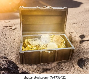 treasure chest filled with bitcoins surrounded by golden glow partially burried in sand on beach
