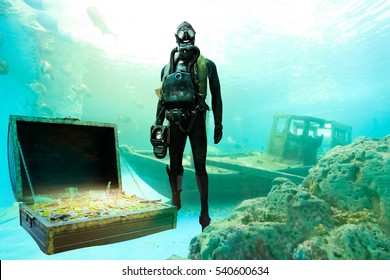 Treasure hunter with mask and snorkel diving underwater among the ancient boat to treasure chest