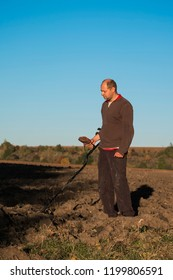 Treasure hunter with a metal detector in his hands with a serious face scans the soil