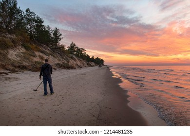 Treasure hunter with metal detector on sunset beach