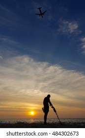 Treasure hunter with Metal detector on sunset  the beach  a plan in the sky