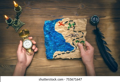 Treasure map ,hand and compass on wooden table. Treasure hunt background. Adventurer man holding in one hand compass and treasure map in another hand and research it.