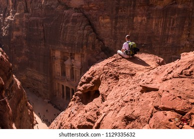 Treasury from above with a hiker, solo traveler, young man backpacker seated on a cliff after reaching the top, Al Khazneh in the ancient city of Petra, Jordan, UNESCO World Heritage Site