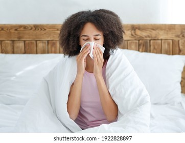 Treat at home, feeling unwell, symptoms of illness and self-isolation. Sad young african american woman sits on bed in blanket and wipes nose with napkin, in interior of cozy bedroom, free space