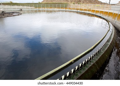Treated wastewater flows over weirs in a wastewater treatment plant clarifier, while bacteria sludge settles at the bottom